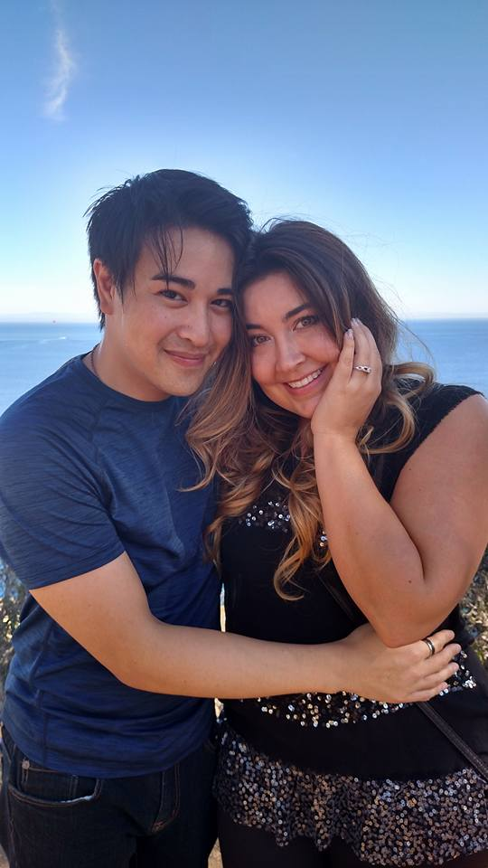 The happily engaged couple, showing off their special engagement ring made by Takayas