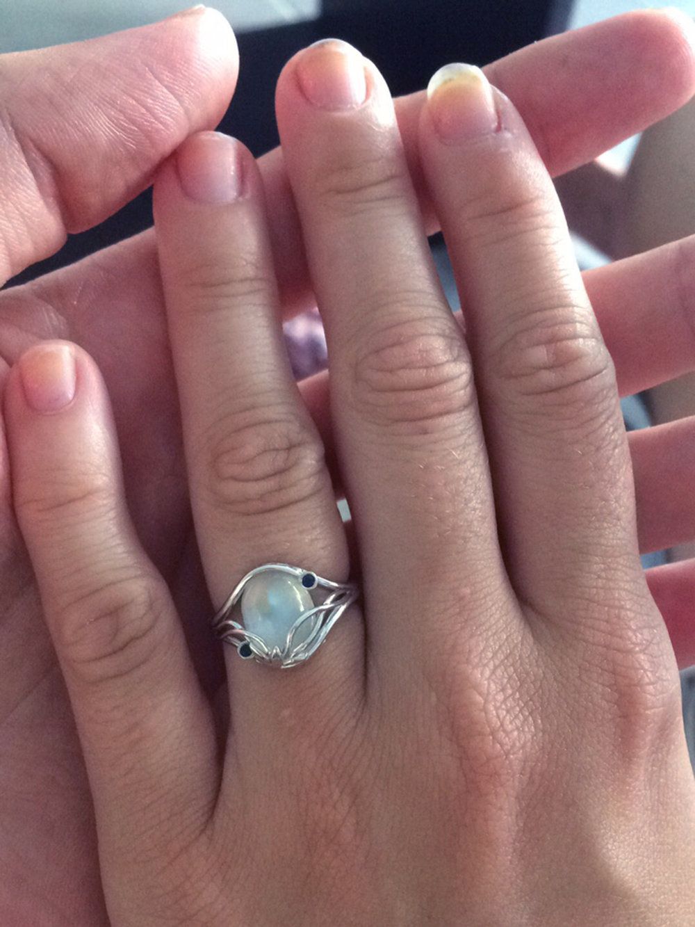 Alice's hand held by Michael's, showing off her new Elvish Moonstone engagement ring by Takayas