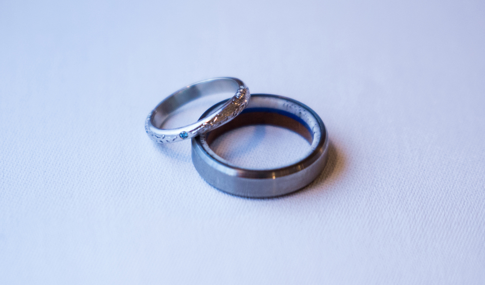 Samantha's custom sylleblossom inspired wedding ring next to her husband's wedding band